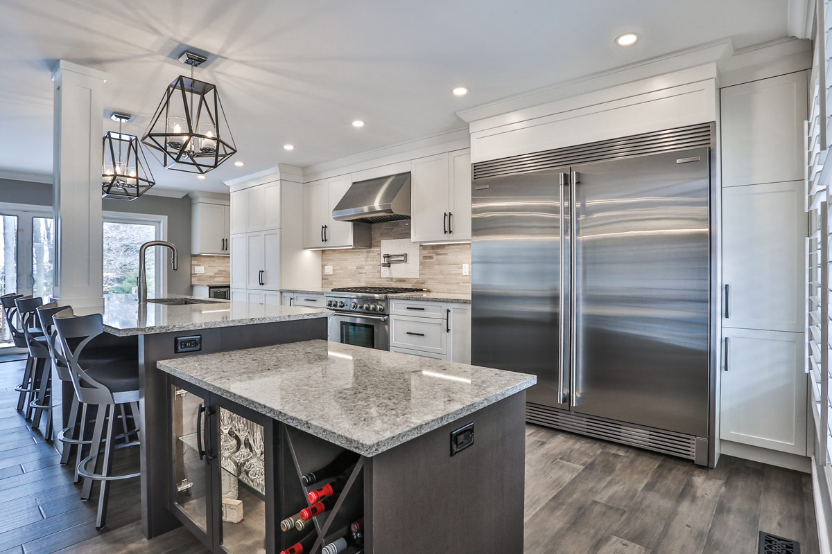 Modern transitional kitchen with with a combination of white and rich brown cabinets, stainless steel appliances, marble countertops, a massive island with built in mini fridge and wine rack, large pantry, all open to the living and dining room. Design and renovation by Total Living Concepts in Barrie, Ontario