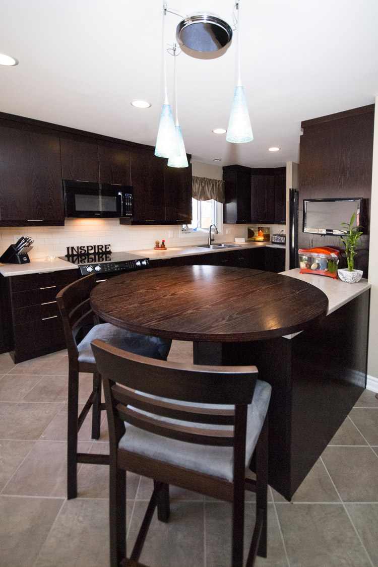 Open concept kitchen with dark wood cabinets, black appliances, and unique round bar table - total living concepts barrie ontario