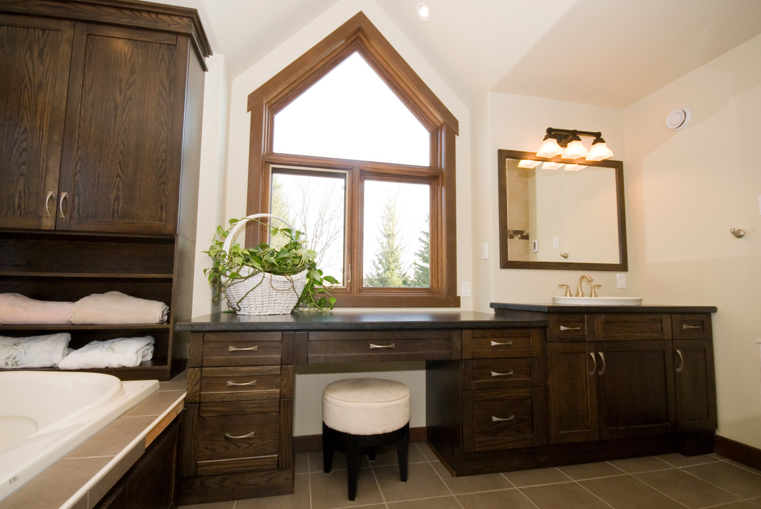 Gorgeous large ensuite bathroom design and renovation in barrie ontario with dark cabinets and makeup desk