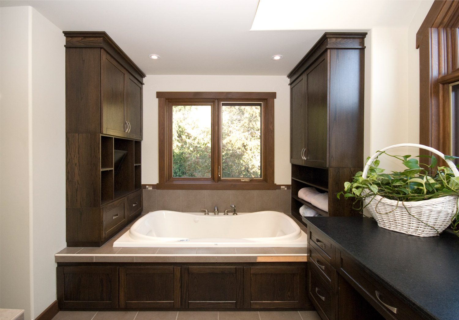 large ensuite bathroom design and renovation in barrie ontario with dark cabinets and soaker tub with TV
