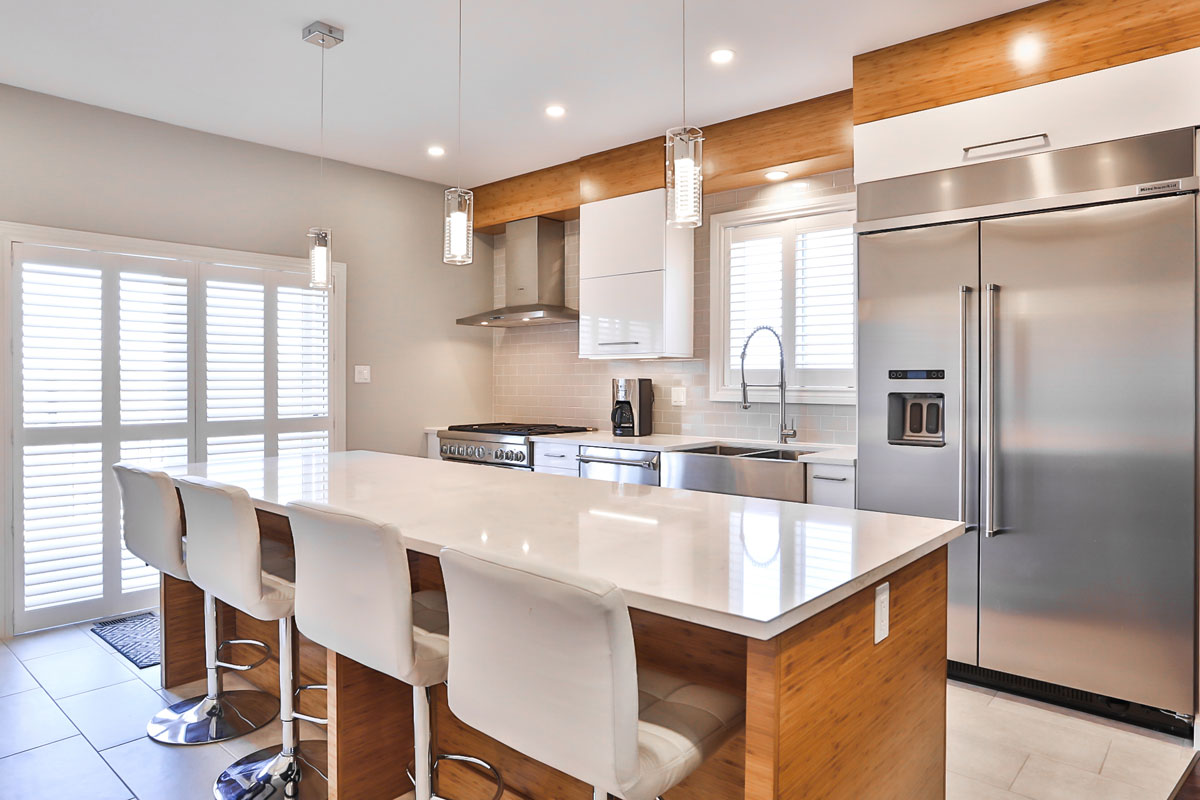 Open concept main floor kitchen and living room featuring gleaming white kitchen cabinets and countertops, stainless steel appliances, a large island with eating bar seating, subway tile backsplash, and wood accents throughout