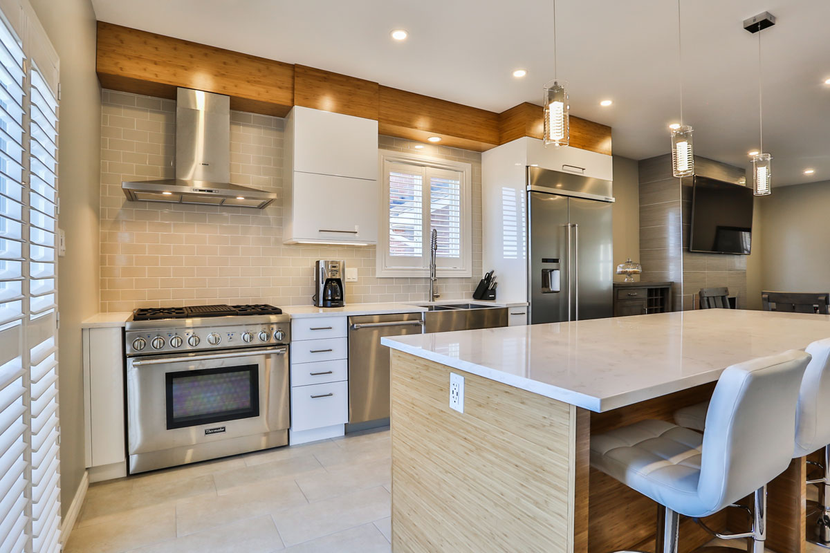 White kitchen design in Barrie Ontario with light tile flooring and subway tile backsplash, stainless steel appliances, and raw wood accents