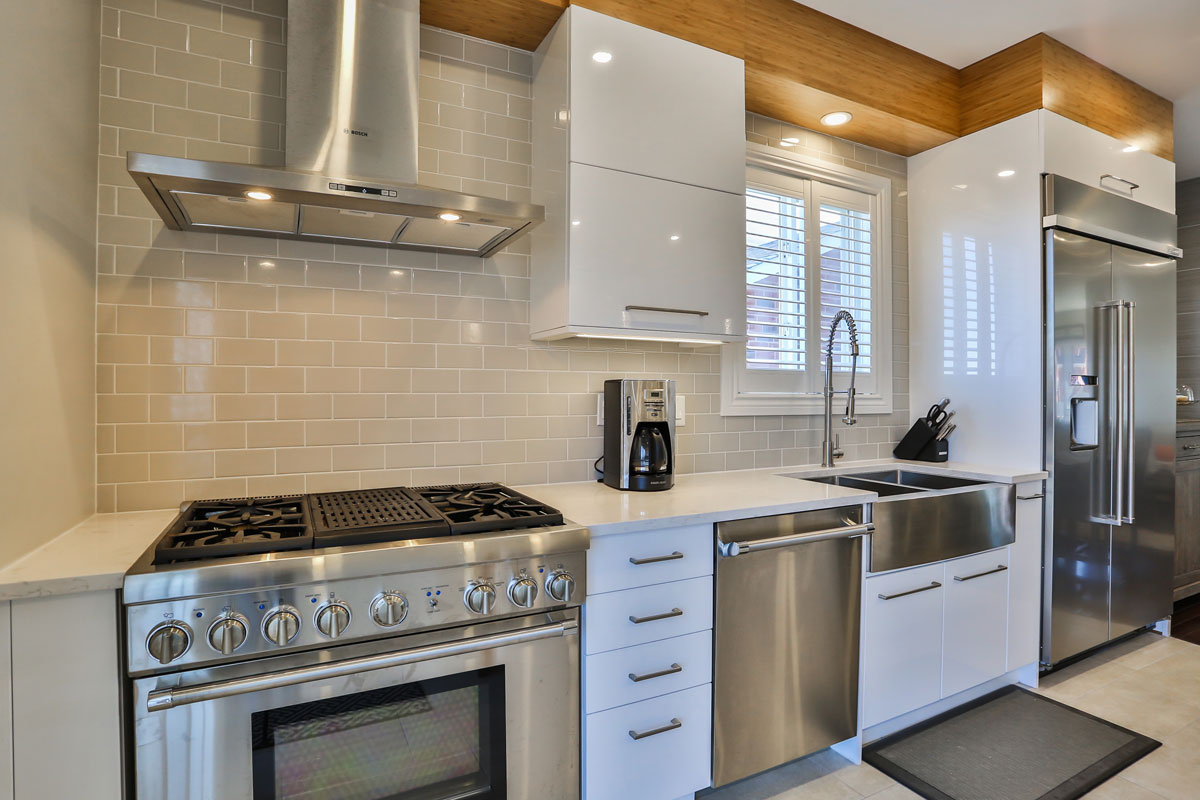 Kitchen design with high end stainless steel appliances and stainless steel farm sink with glossy white appliances