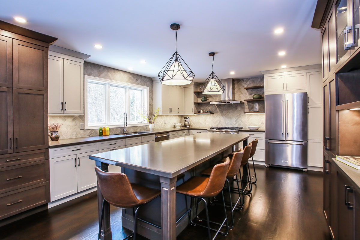Transitional kitchen design and renovation featuring a large island with eating bar, stainless steel appliances, ivory and warm brown cabinets, dark wood hardwood floors - barrie kitchen reno and design by total living concepts