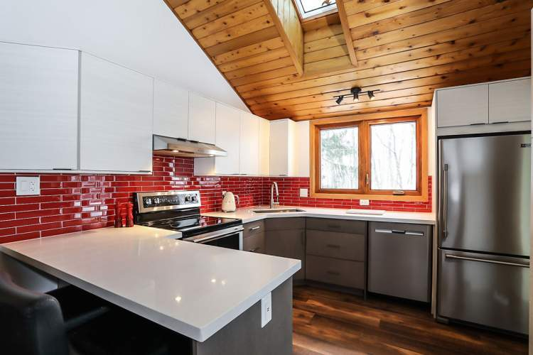 Kitchen renovation featuring two-toned white and warm grey cabinets, clean white countertops, stainless steel appliances, natural wood flooring, and red tile backsplash for a pop of colour.