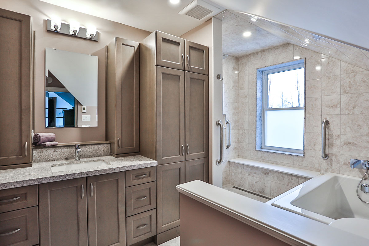 Ensuite bathroom design Barrie Ontario with a large soaker tub and separate shower, lots of built in cabinets and laundry