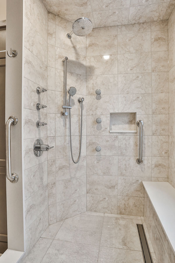 Ensuite bathroom design with standup shower featuring a bench and rain shower