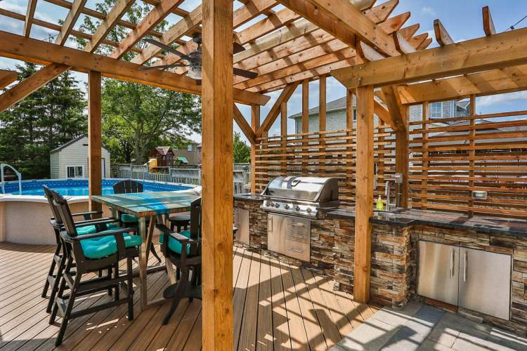 Backyard redesign with natural wood, large patio, pool and stainless steel appliances.