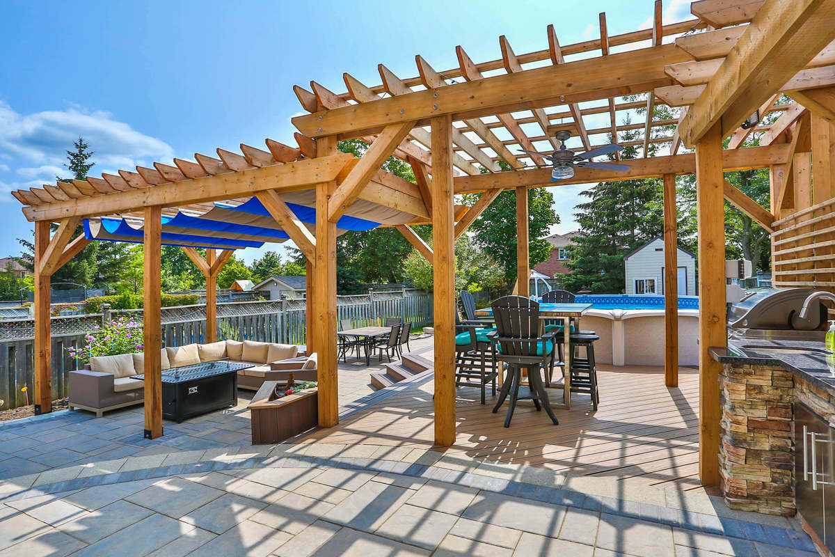 Backyard redesign with natural wood, generous seating, large patio, pool and stainless steel appliances.