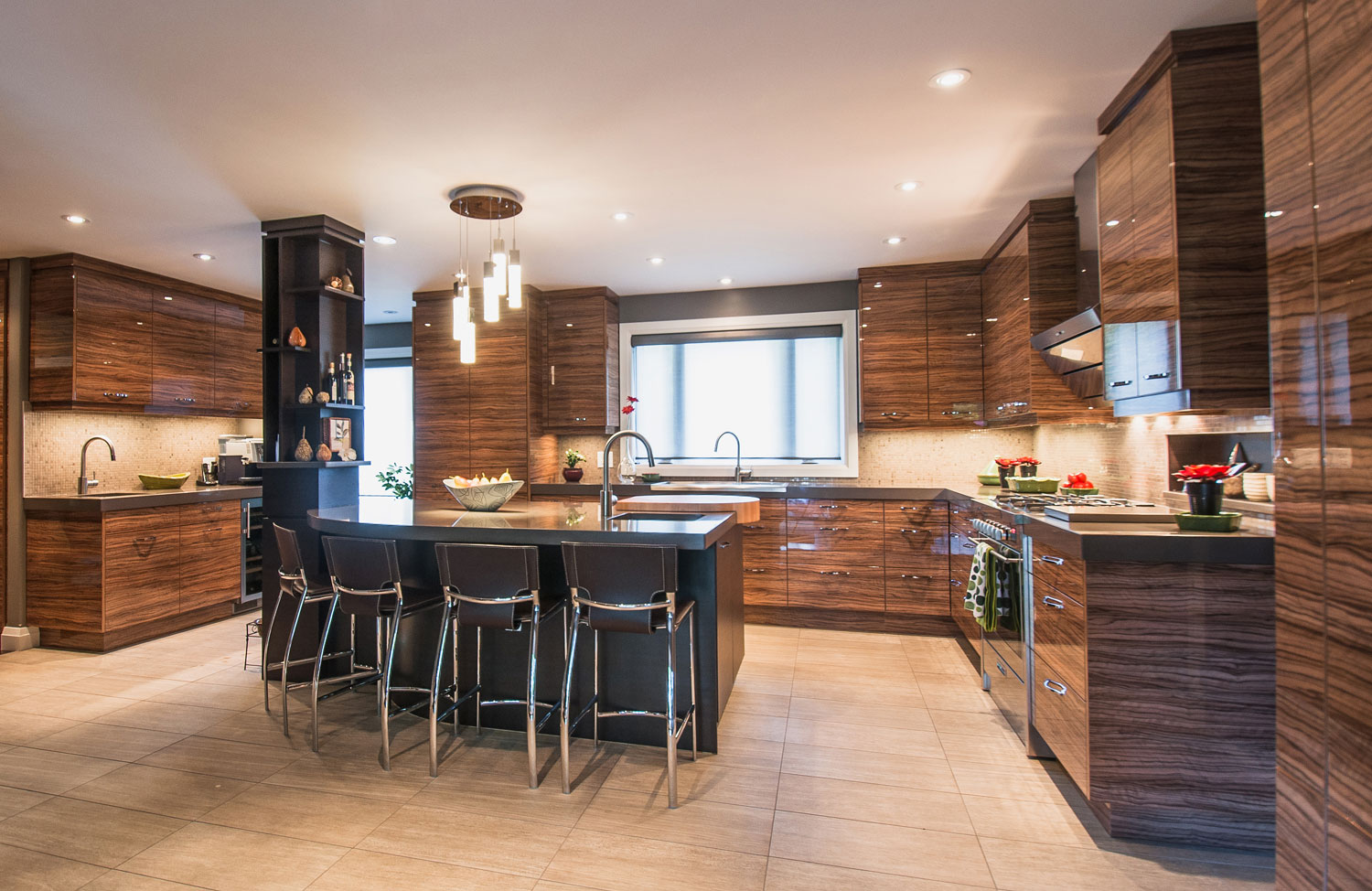 Large kitchen with bamboo style cabinets, stainless steel appliances, hidden fridge, bar area with wine fridge, and large curved island with cutting block built into the countertop - Total Living Concepts barrie ontario