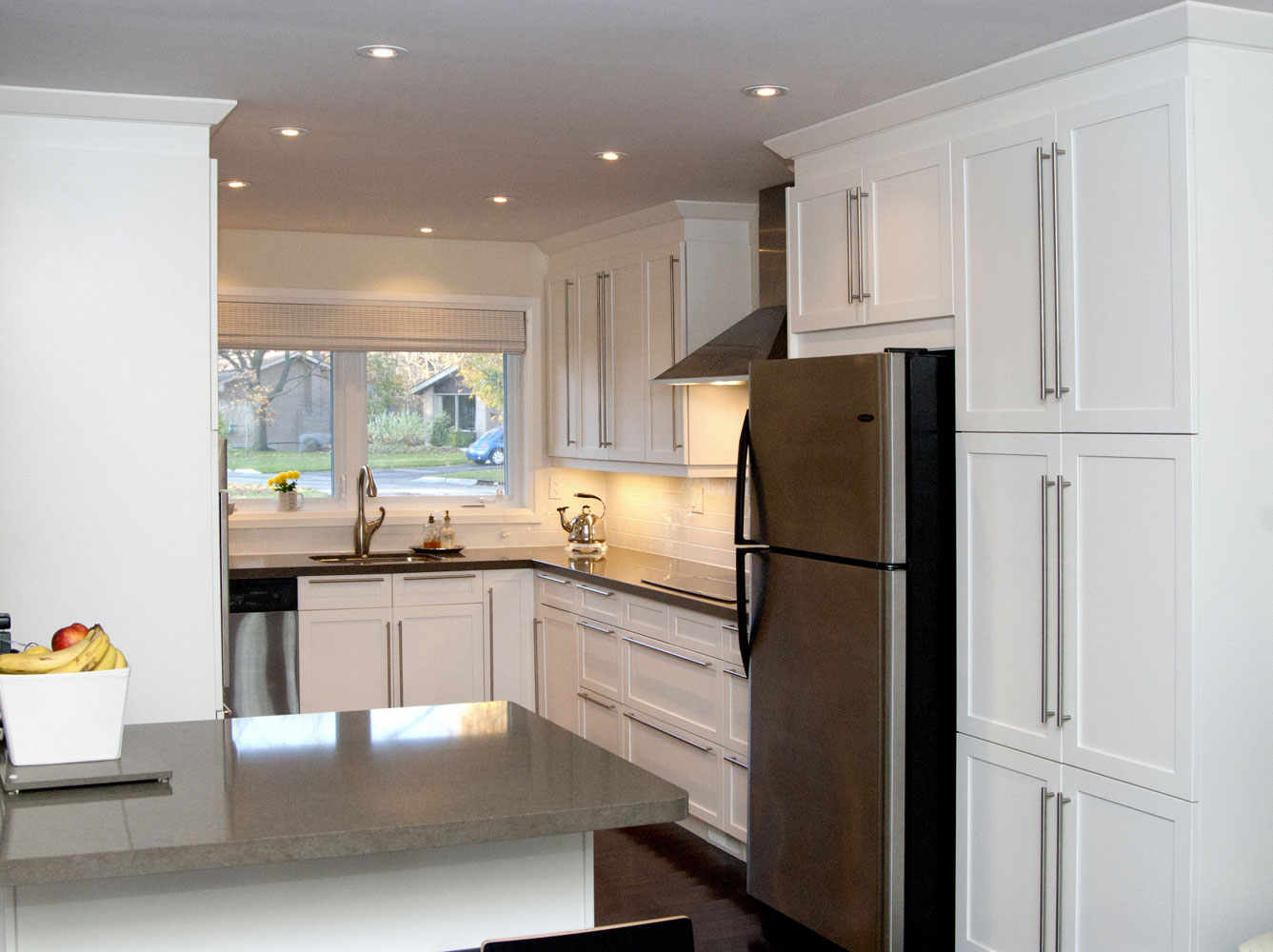 Clean white u-shaped kitchen design with dark hardwood floors and stainless steel appliances