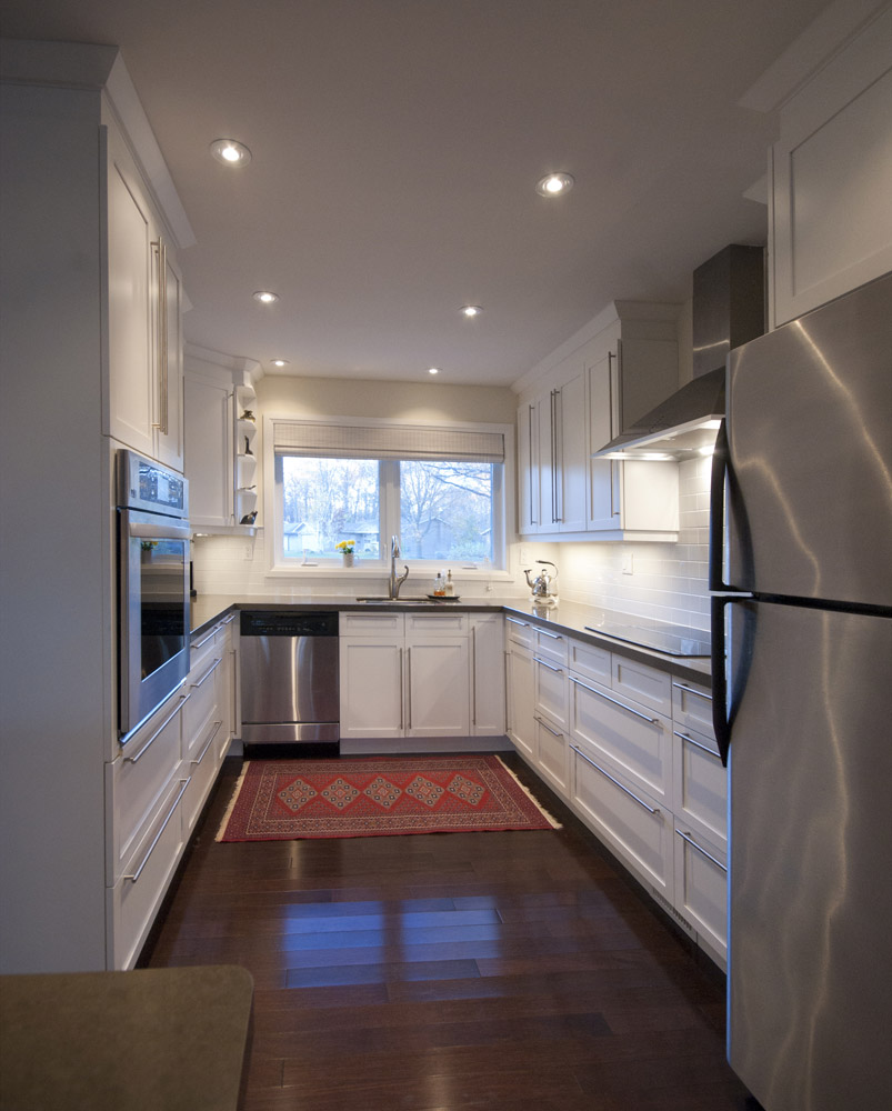 Open concept white kitchen design with dark hardwood floors and stainless steel appliances - Total Living Concepts barrie ontario