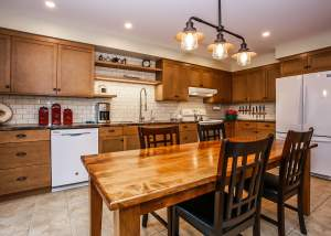 Eat-in country kitchen with wood cabinets, white appliances, and subway tile backsplash - Total Living Concepts barrie ontario