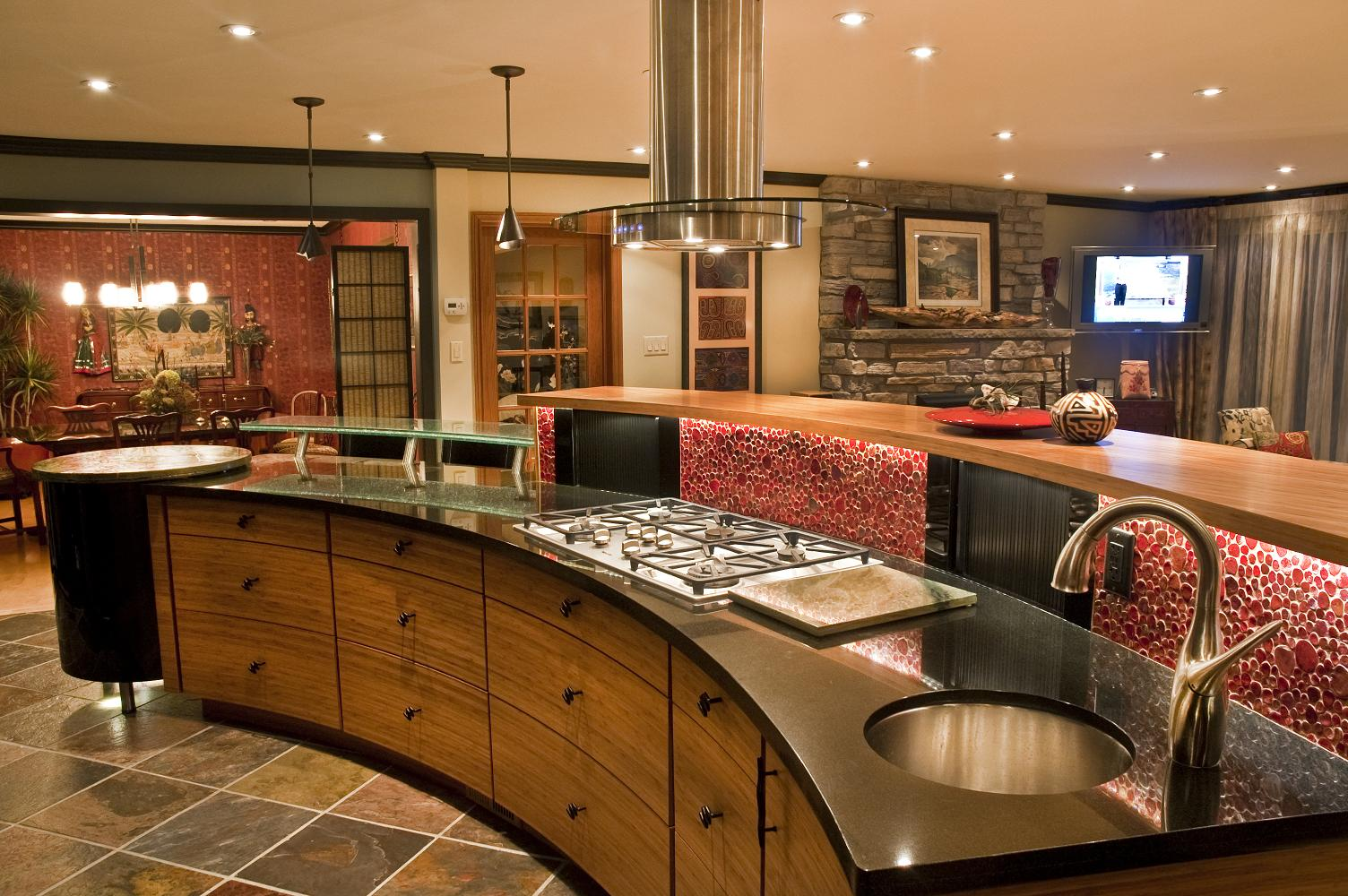 Eclectic kitchen design with curned island, black countertops, wood cabinets, and a floating hood fan