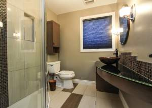 Eclectic modern main bathroom that features curved elements including a curved shower wall and vanity, round vessel sink, and circular mirror - Total Living Concepts in barrie ontario