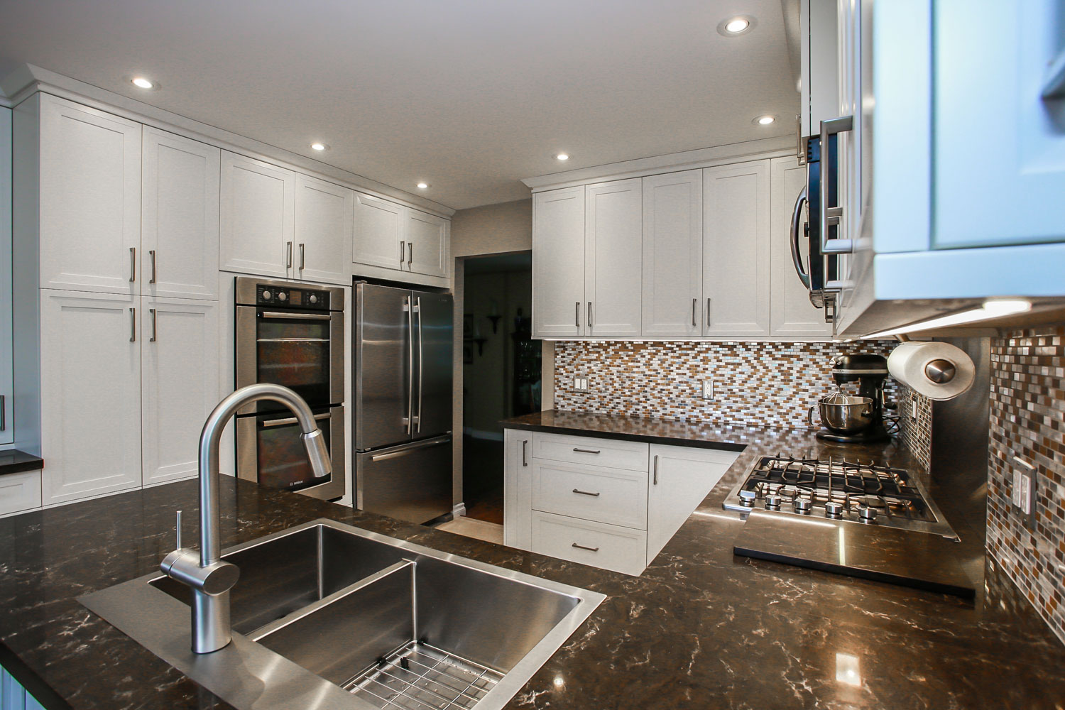 White kitchen with stacked wall ovens and built-in microwave and granite counter tops - Total Living Concepts barrie ontario