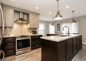 Kitchen design with large island with eating bar, warm grey and dark brown cabinets, stainless steel appliances, and stunning mosaic backsplash - total living concepts in barrie ontario