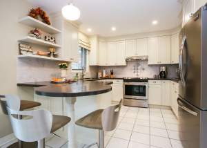 French Country Kitchen with white cabinets, white tile flooring, black counter tops, stainless steel appliances