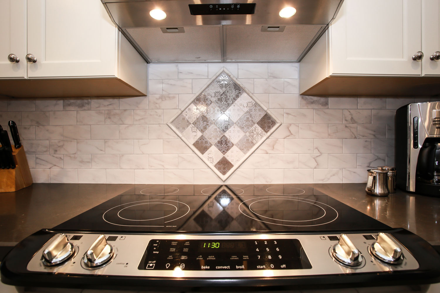 Mosaic pattern in backsplash behind kitchen stovetop