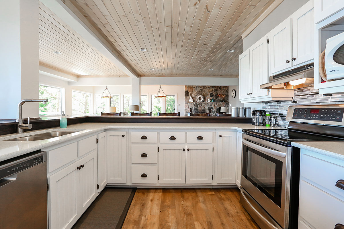 Georgian Bay Cottage Kitchen with farmhouse style white cabinets, plank hardwood flooring, stainless steel appliances, and a wood ceiling with white beams
