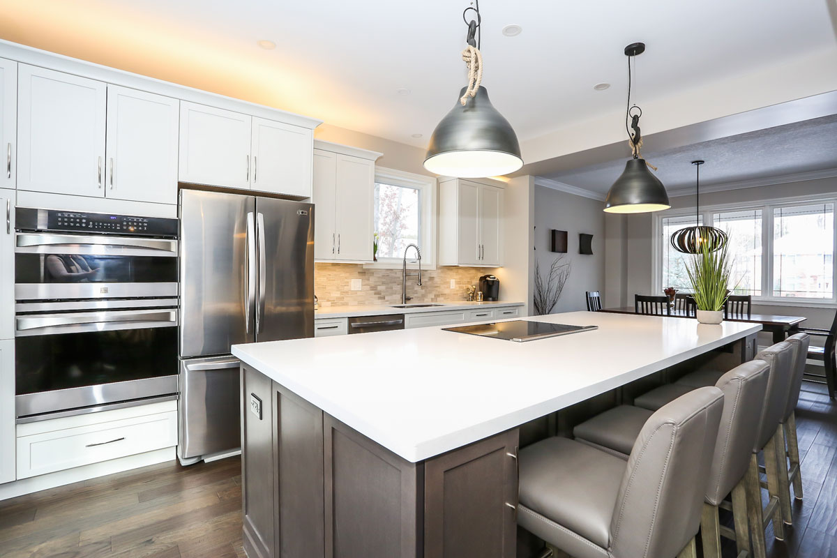 Open concept transitional kitchen with white cabinets and stainless steel appliances - design and renovation by total living concepts in barrie ontario