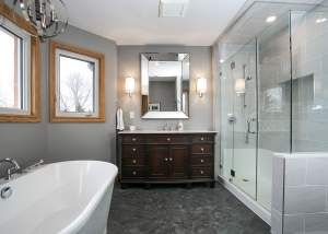 Ensuite bathroom renovation with floating soaker tub, large glass shower, and dark wood cabinetry