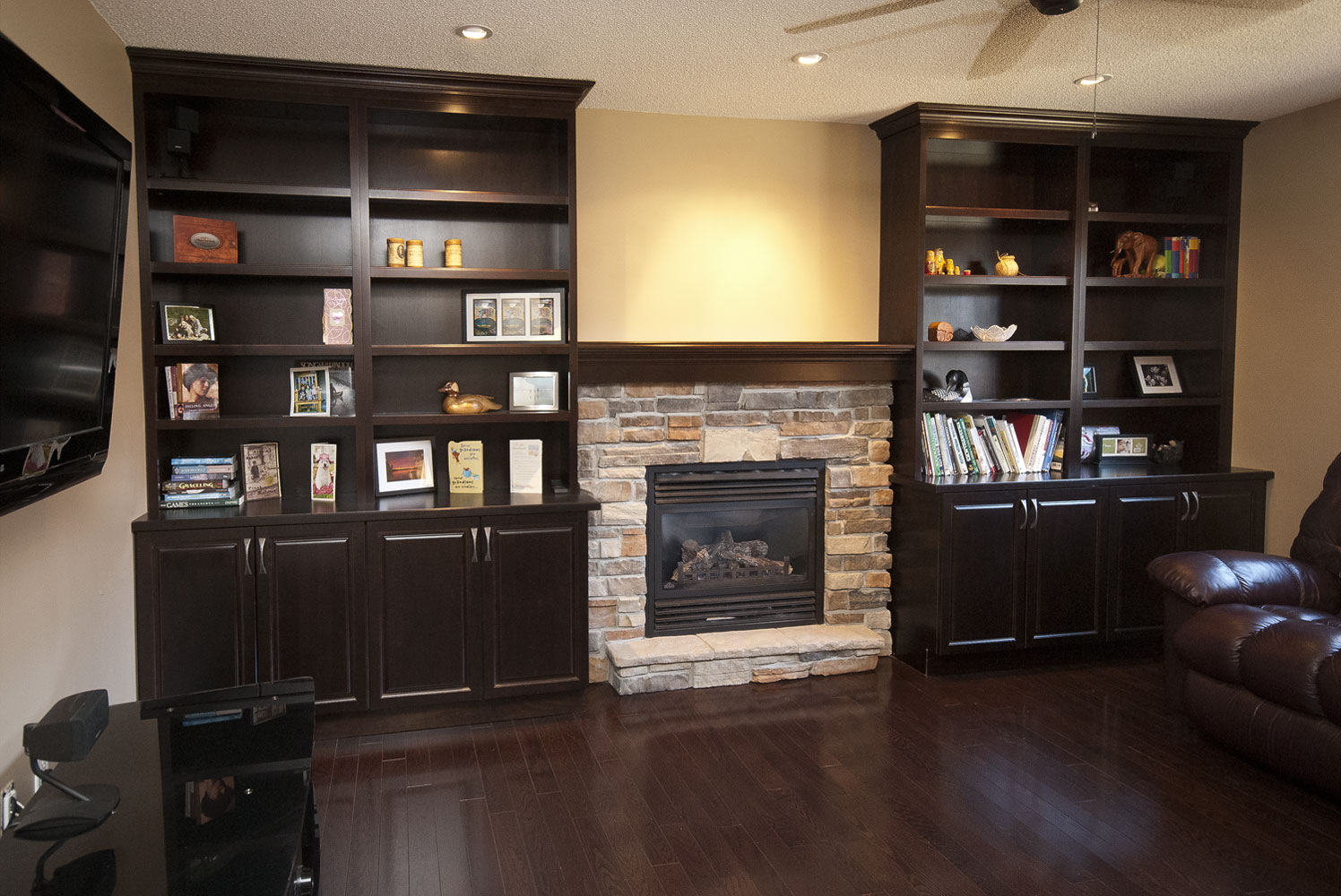 Basement living room renovation with gas fireplace and built-in shelving and storage - Total Living Concepts barrie ontario