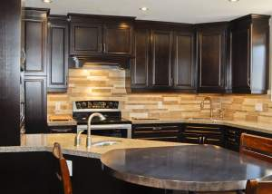 Warm kitchen design utilizing dark and light brown tones throughout including dark wood cabinets, hardwood floors, and backsplash, with stainles steel appliances and unique round steel eating bar - Total Living Concepts barrie ontario