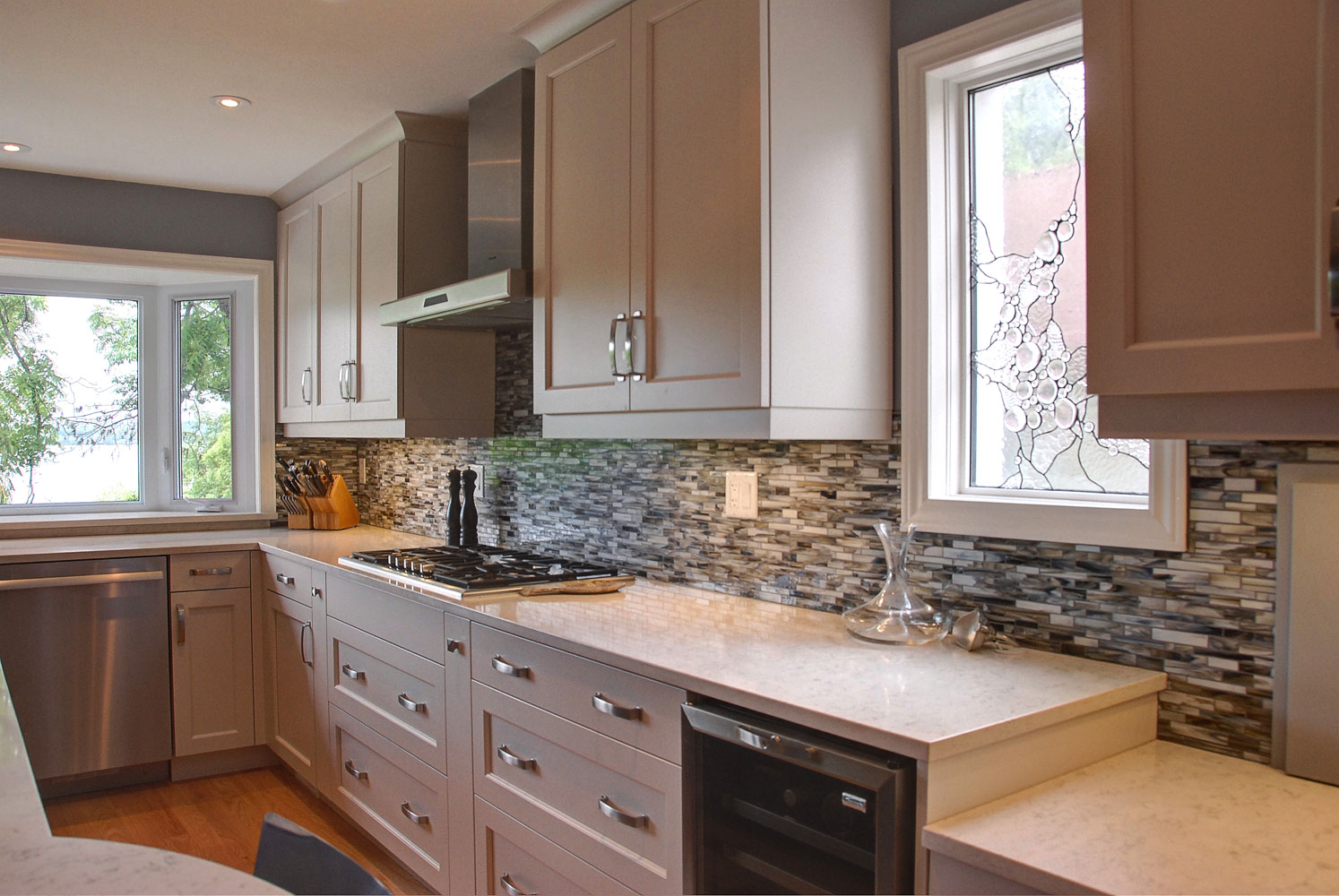 Cream kitchen cabinets with stainless steel appliances and accents - Total Living Concepts ontario