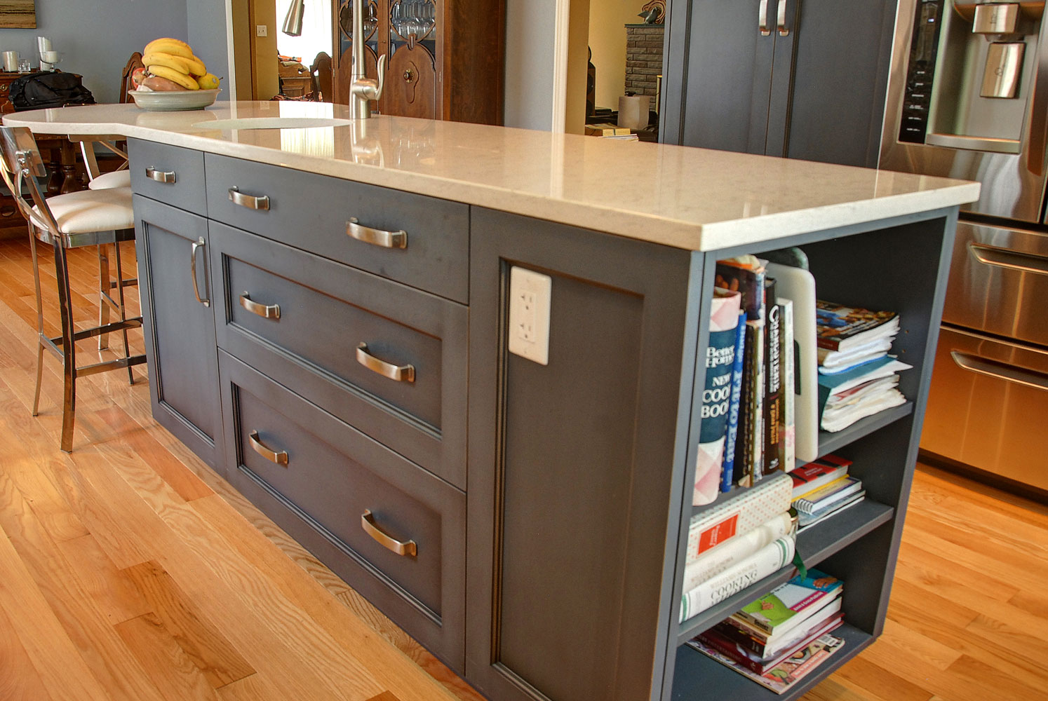 Kitchen island with open cabinets on one end and rounded counter on other end