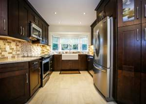 Transitional kitchen design and renovation that combines traditional and contemporary elements with dark wood cabinets, stainless steel appliances, and a farmhouse apron sink - Total Living Concepts barrie ontario