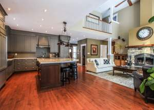 Open concept kitchen with warm earth tones including grey kitchen cabinets with dark wood cabinets on the island - Total Living Concepts barrie ontario