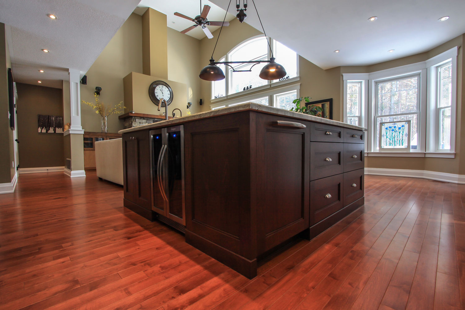 Kitchen island with dark wood cabinets, hidden dishwasher, and bar fridge - Total Living Concepts barrie ontario