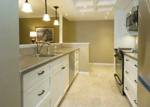 White and grey galley kitchen design featuring white cabinets, stainless steel appliances, tile flooring, and coffered ceiling - Total Living Concepts barrie ontario