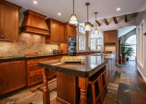 Large wood kitchen design with wood cabinets and island, granite counter tops, stainless steel appliances, tile flooring, wood ceiling beams, and vaulted windows - Total Living Concepts in Barrie Ontario