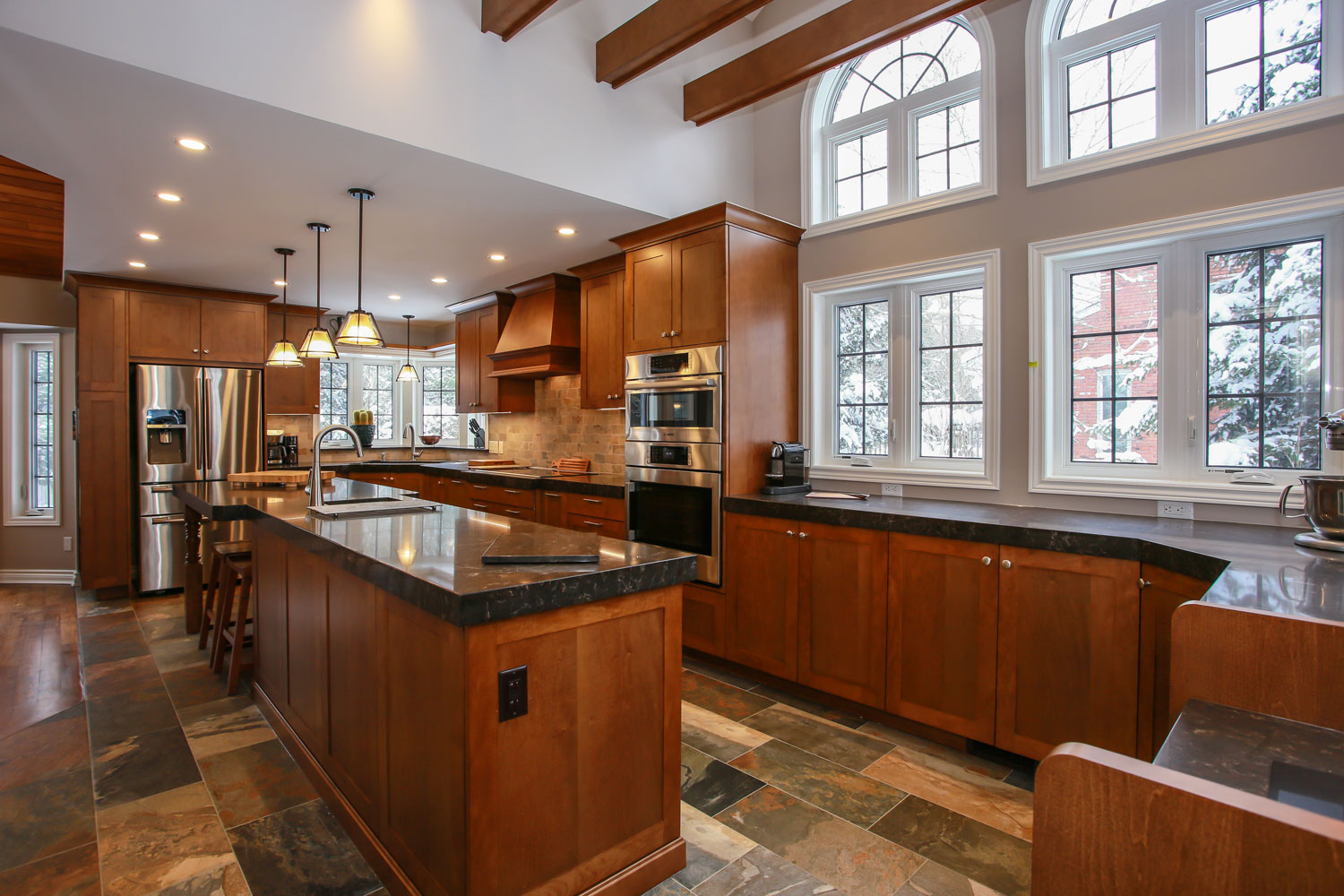 Luxury open concept kitchen with rich wood cabinets, granite countertops, vaulted ceiling with wood ceiling beams and arched windows - Total Living Concepts barrie ontario