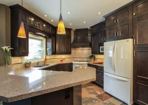 Kitchen renovation with dark wood cabinets and earth tones - Total Living Concepts barrie ontario