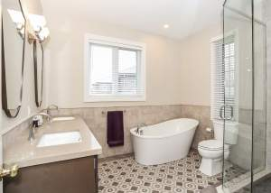 Gorgeous ensuite design with dual sinks, freestanding tub, stand up glass shower with rock floor, and beautiful tile floor pattern - Total Living Concepts in barrie ontario