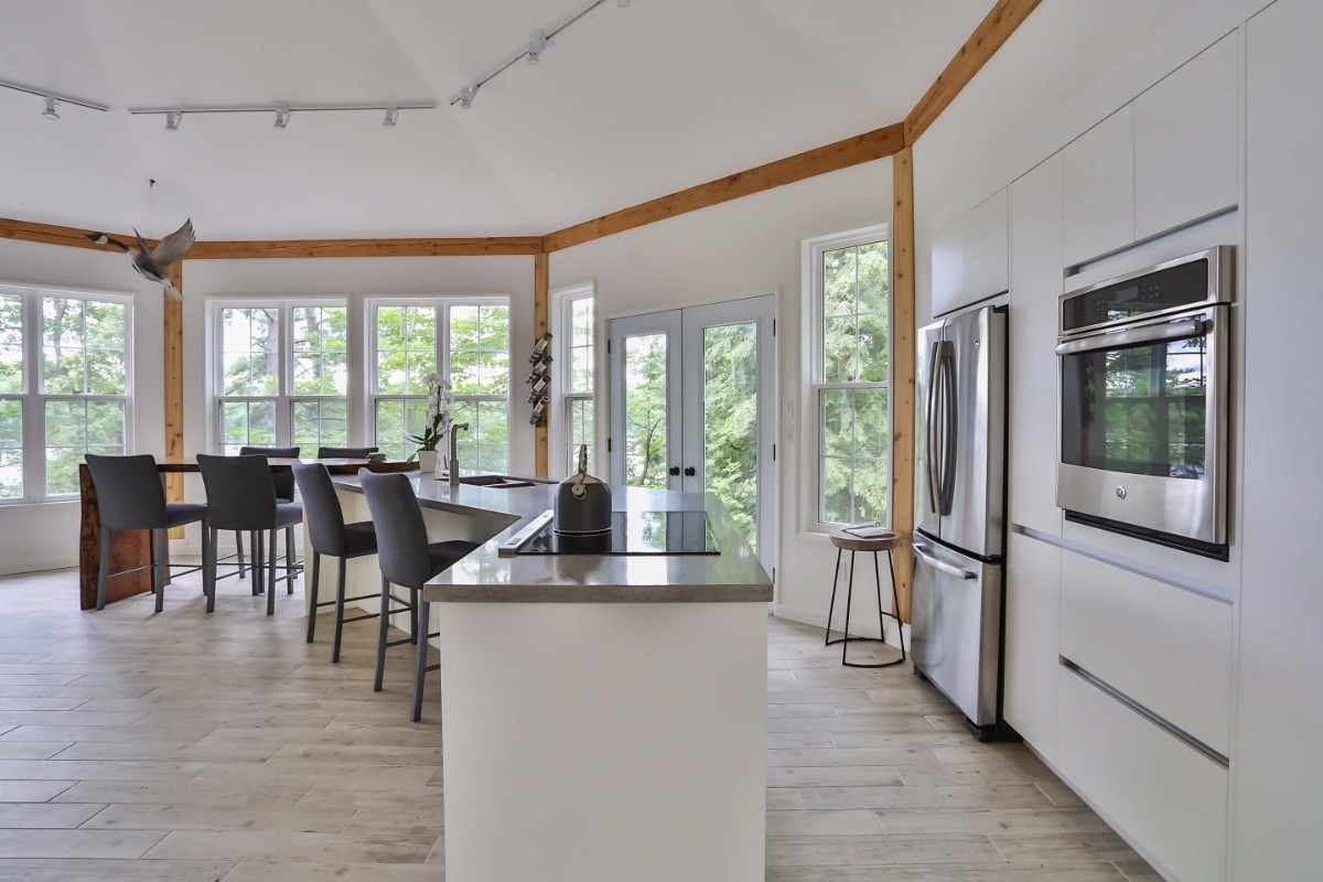White, open concept kitchen with an island and stainless steel appliances.