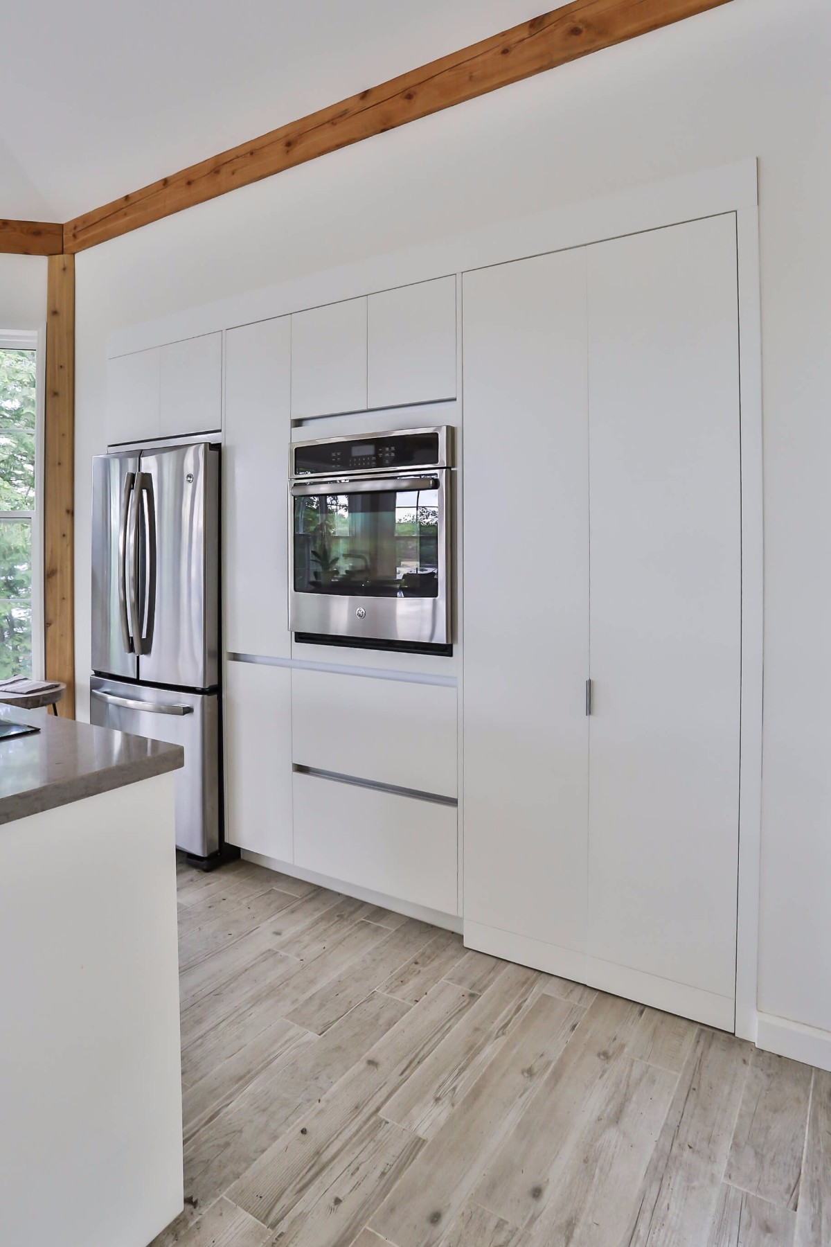 White kitchen cupboards, hardwood floors and stainless steel appliances.