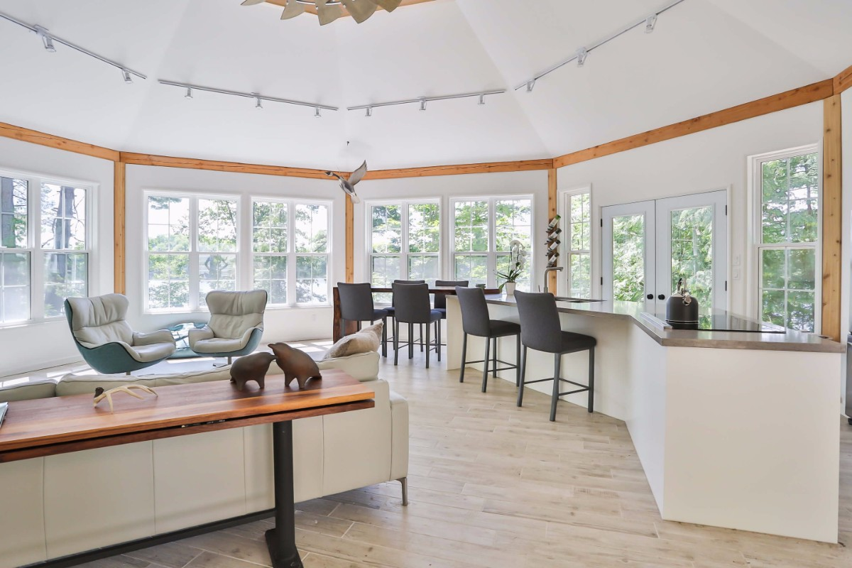 Bright, open concept white kitchen design with hardwood floors and a long island.