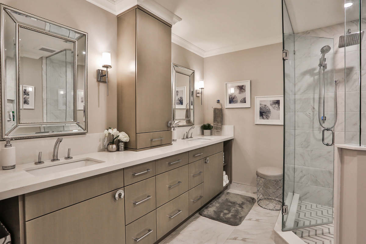 Modern bathroom with tile floors, glass shower and generous storage space.