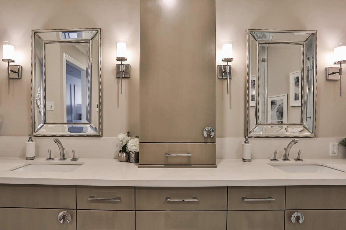 Modern bathroom with tile floors, modern light fixtures and generous storage space.