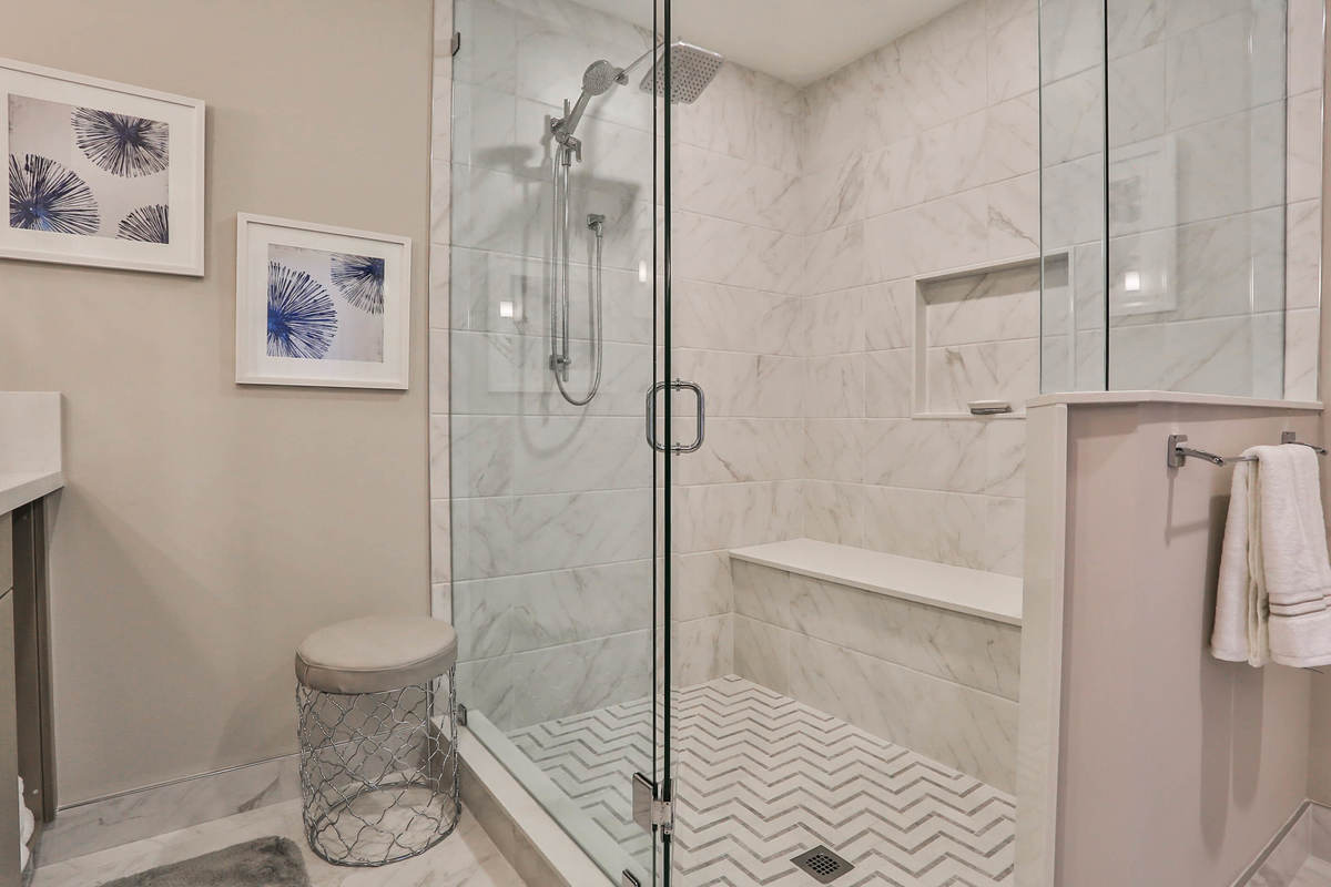 Modern bathroom with tile floors and large glass shower.