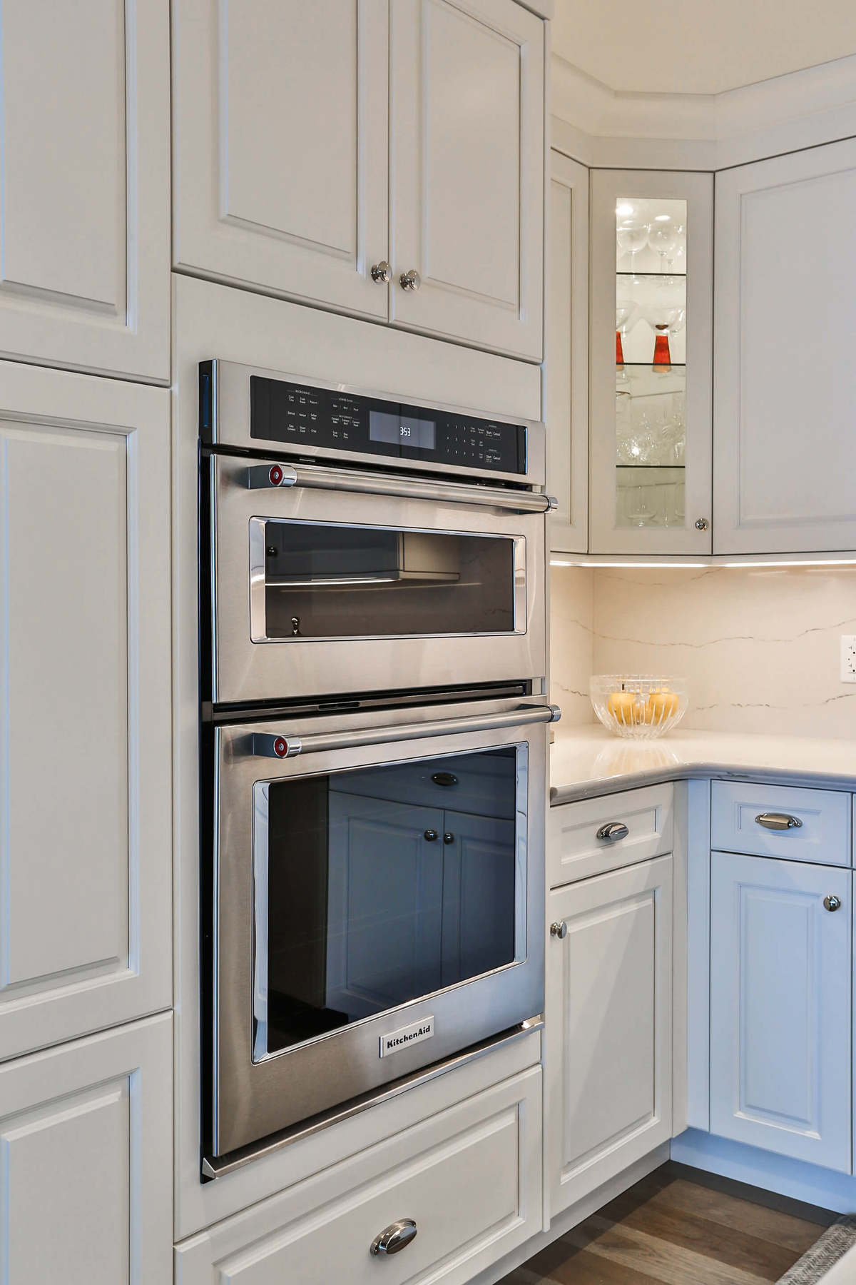 White kitchen design with white cupboards, stainless steel appliances, generous storage and hardwood floors.