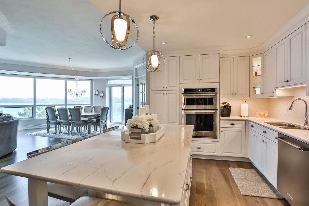 White kitchen design with white cupboards, stainless steel appliances, hardwood floors, and a large island.