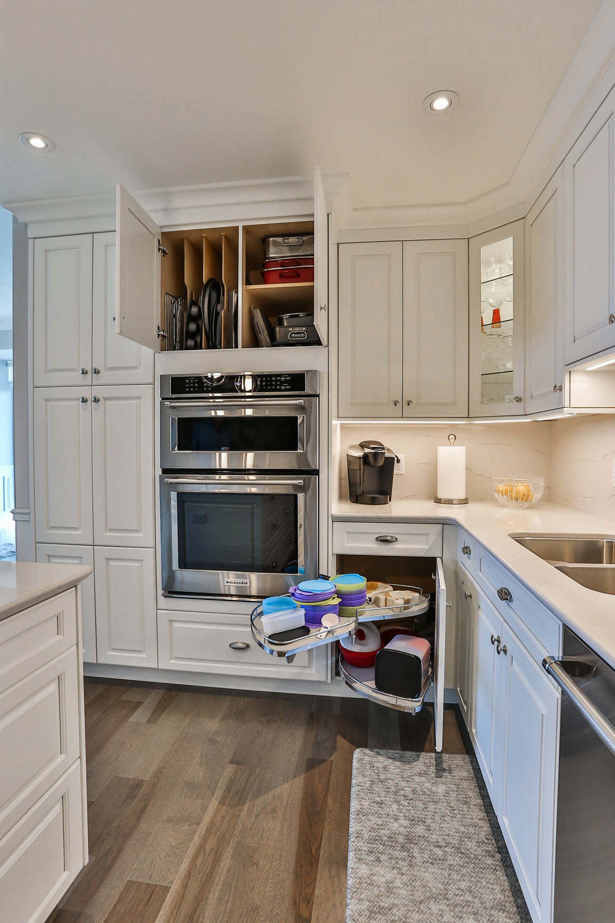 White kitchen design with white cupboards, stainless steel appliances, hardwood floors, and a generous storage.