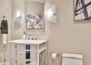 White bathroom design with tile flooring and modern light fixtures.