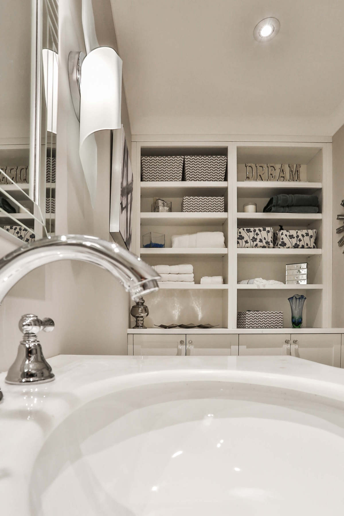 White bathroom design with modern fixtures and generous wall storage.