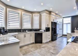 White kitchen design with a large island, white cupboards, and tile floors.